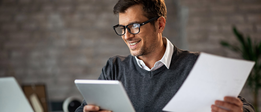 young male accountant looking at papers and computer
