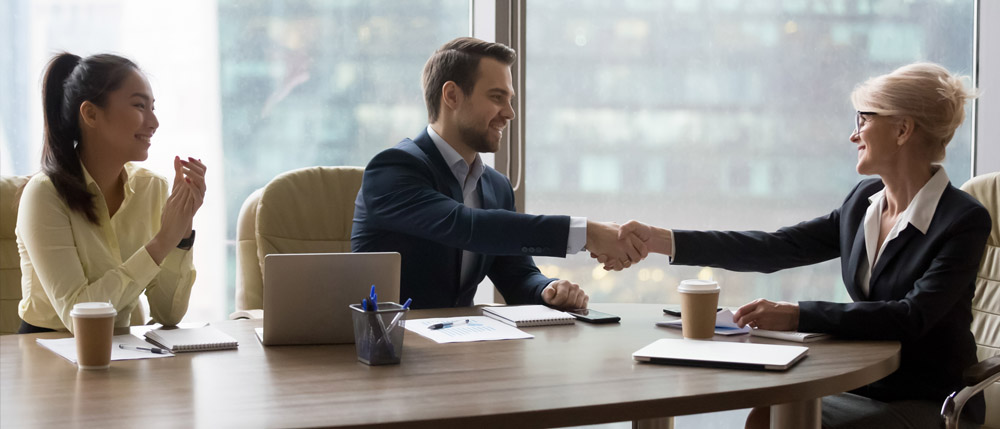 young accountant shaking hands with new boss