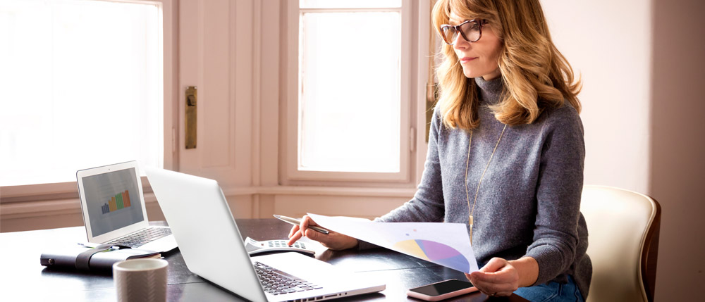 female tax firm owner looking at laptop