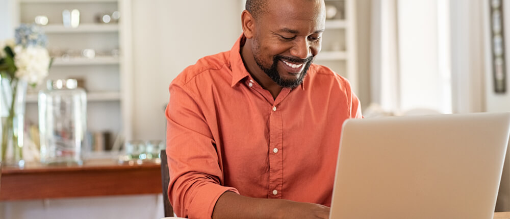 young male accountant working on laptop at home